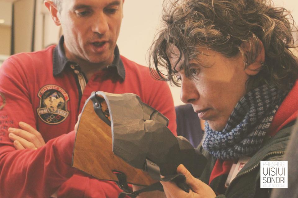 Paola ascolta la descrizione di Mario della maschera che ha in mano, nel corso del secondo incontro del laboratorio sulle disabilità visive per Paesaggi visivi e sonori di Mamoiada