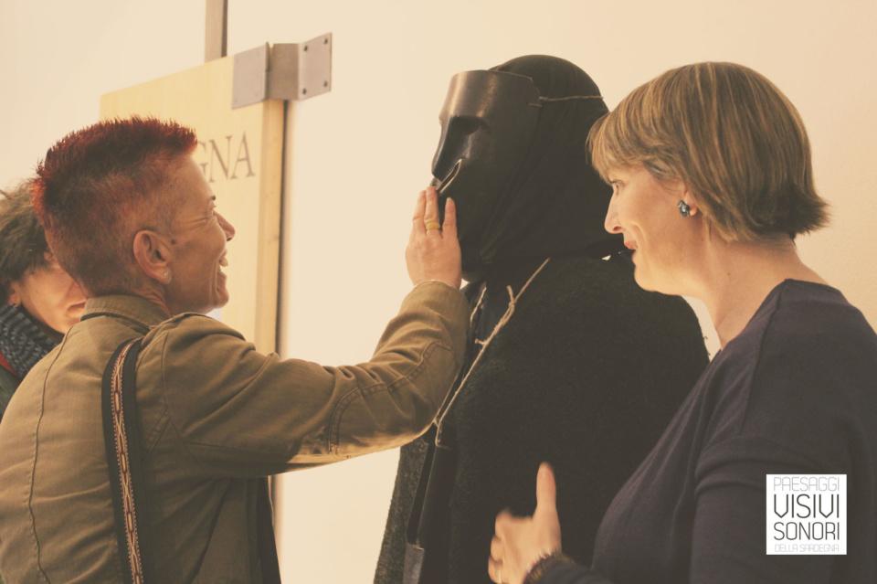 Monica ascolta la descrizione di Rita della maschera de Sa Filonzana, nel corso del secondo incontro del laboratorio sulle disabilità visive per Paesaggi visivi e sonori di Mamoiada